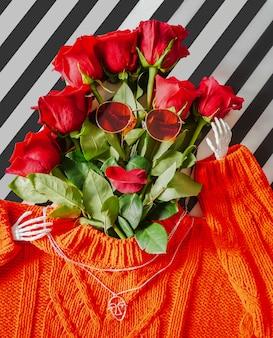 Rote strickjacke mit einem blumenstrauß von roten rosen und von gläsern auf einem hellen hintergrund.