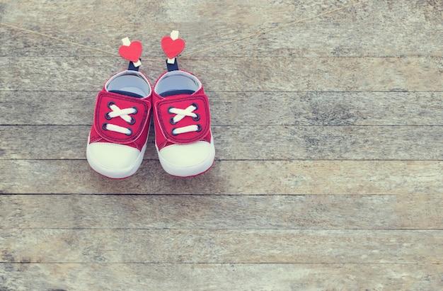 Rote süße babyschuhe, die mit herzförmigen wäscheklammern an der holzwand hängen