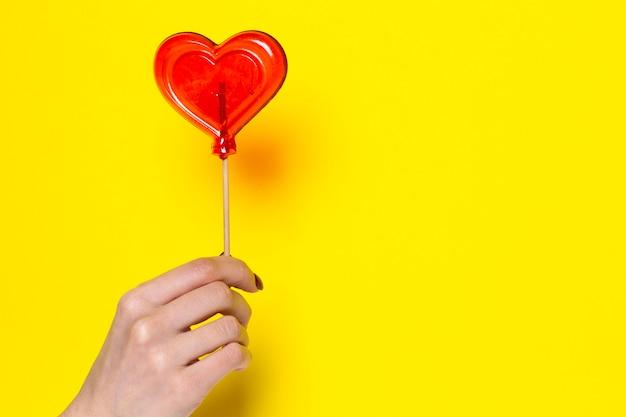 Rote süßigkeit in form eines herzens in einer weiblichen hand auf einem gelben.