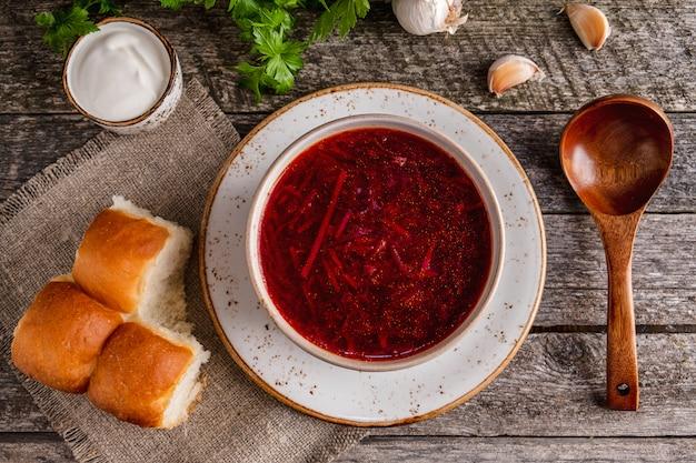 Rote suppe der traditionellen ukrainischen küche rote rübe, kartoffel, fleisch, karotte, kohl und knoblauch. ansicht von oben.