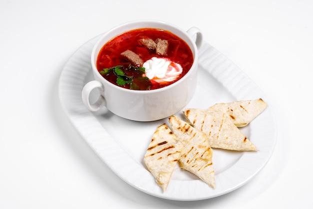 Rote suppe in einem weißen teller. borschtsch mit brotvorspeise.