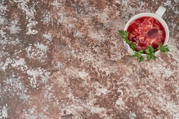 Rote suppe in einer weißen tasse.