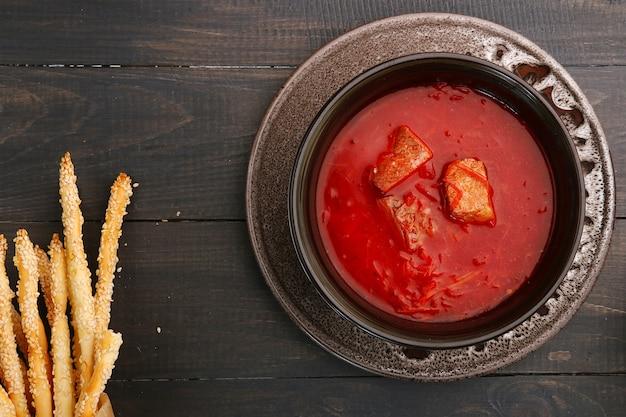 Rote suppe namens borschtsch mit fleischstücken und gewürzen auf schwarzem holztisch mit grissini. traditioneller ukrainischer russischer borschtsch