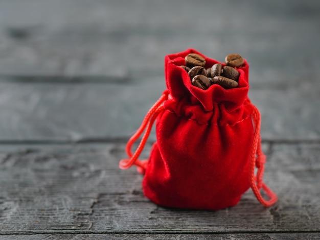 Rote tasche mit geröstetem kaffee auf einem dunklen rustikalen tisch