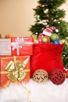 Rote tasche mit weihnachtsspielzeug auf weihnachtsbaumhintergrund