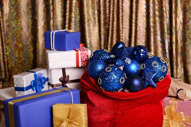 Rote tasche mit weihnachtsspielzeug und geschenken auf stoffhintergrund