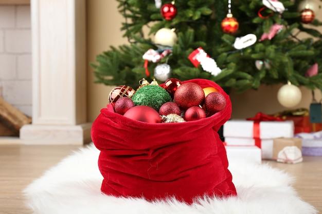 Rote tasche mit weihnachtsspielzeug und geschenken im zimmer