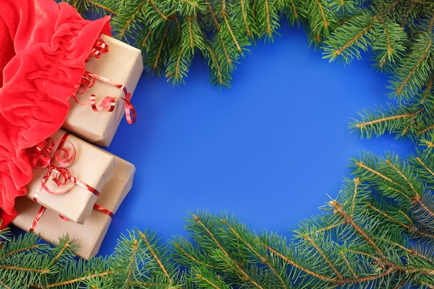 Rote tasche santa clauss mit geschenken und weihnachtsbaum auf blauem hintergrund.