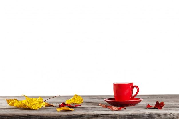 Rote tasse auf tisch mit herbstlaub