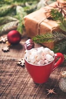 Rote tasse heiße schokolade mit marshmallow- und tannenzweigen, geschenkboxen auf verschneitem winterhintergrund mit schneebedeckten zweigen auf altem holztisch. weihnachts- oder winterkonzept.