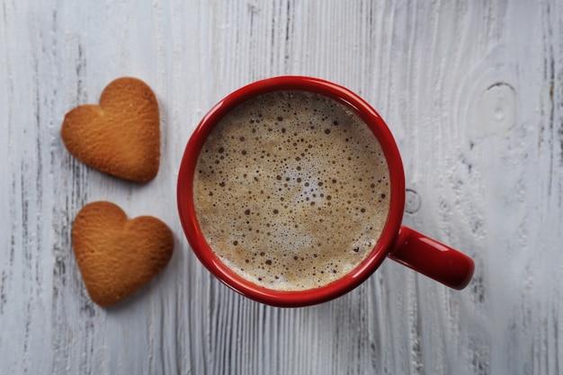 Rote tasse heißen kakaos und herzförmige kekse auf holzoberfläche