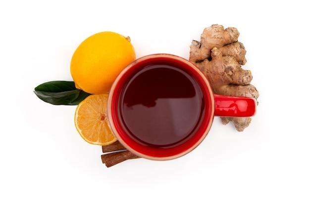 Rote tasse heißen schwarzen oder grünen tees mit zitrone und ingwer auf einem weißen hintergrund. inhaltsstoffe gegen influenza und viren. natürliche medizin.