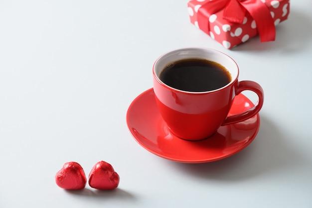 Rote tasse kaffee, herzbonbons und geschenkkekse