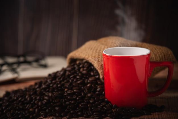 Rote tasse kaffee mit kaffeebohnen