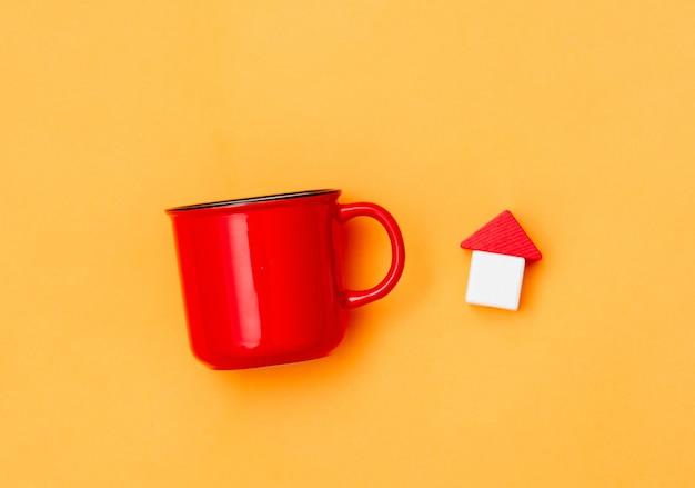 Rote tasse kaffee und hölzernes spielzeughaus auf gelb