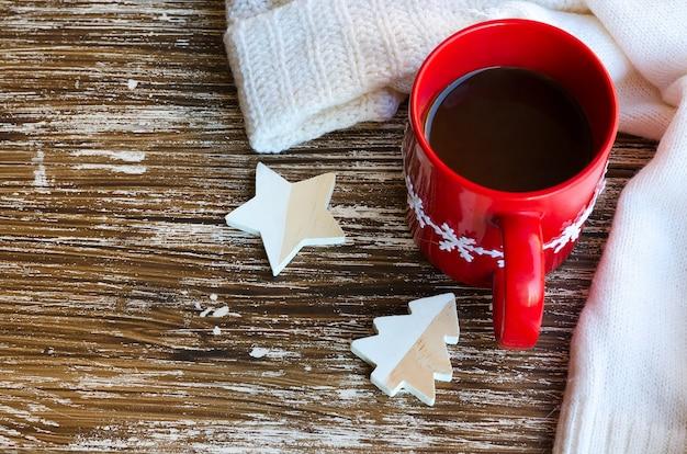Rote tasse kaffee und weißer kuscheliger strickpullover auf der rückseite. köstliches getränk bei kaltem wetter. winterzeiten oder weihnachtsmorgenkonzept.