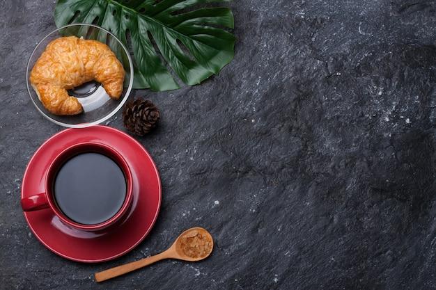 Rote tasse kaffee und zucker im löffel, croissant-kiefer trocken auf schwarzem stein