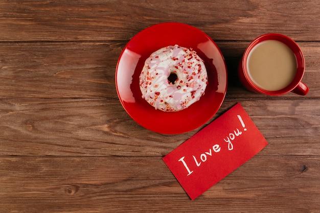 Rote tasse mit donut und liebesbrief