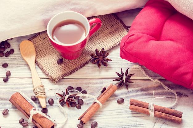 Rote tasse mit espresso, anis, zimt, löffel und kissen