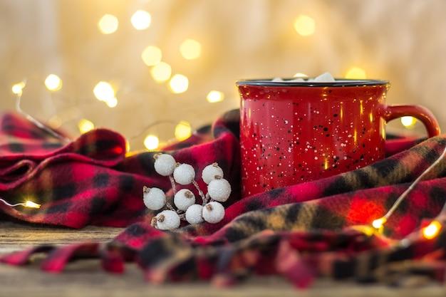 Rote tasse mit heißem kaffeegetränk und süßen marshmallows auf holztisch mit plaid in weihnachtsdekorationen mit beeren und girlande bokeh beleuchtet hintergrund. neujahrsferienkonzept.
