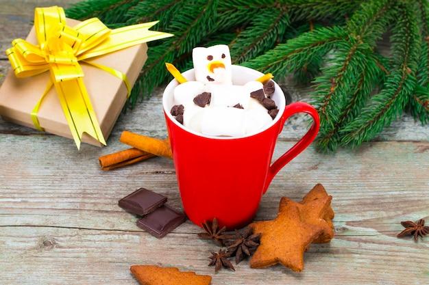Rote tasse mit heißer schokolade mit geschmolzenem marshmallow-schneemann.