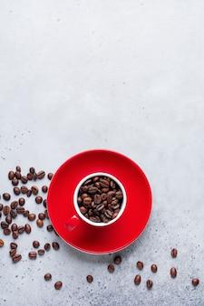 Rote tasse mit kaffeebohnen innen auf grauem beton