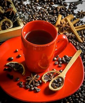 Rote tasse mit kaffeebohnen und gewürzen
