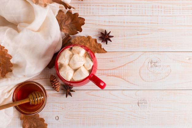 Rote tasse mit kakao und eibischen, auf einem hintergrund eines schals und der trockenen blätter. herbststimmung, ein wärmendes getränk.