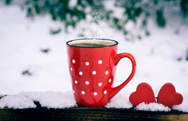 Rote tasse mit tupfen mit heißem schwarzem kaffee