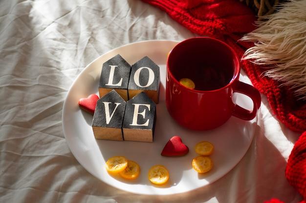 Rote tasse tee mit kumquat auf dem teller und zwei herzplätzchen mit dem wort liebe auf einem weißen bett