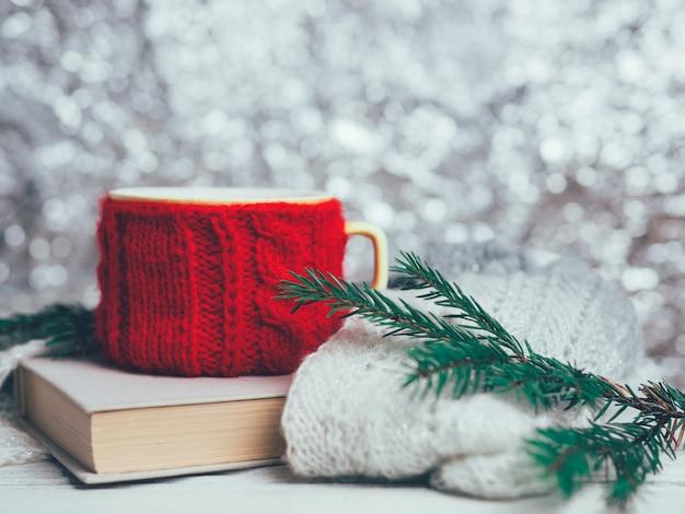 Rote tasse tee oder kaffee mit buch und weihnachtsbaumasten