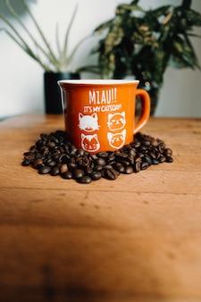 Rote tasse umgeben von kaffeekörnern