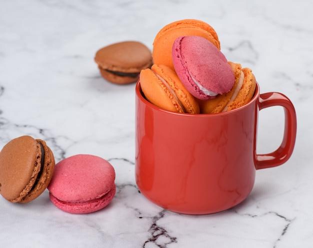Rote tasse und gebackene macarons auf einem weißen tisch, nahaufnahme