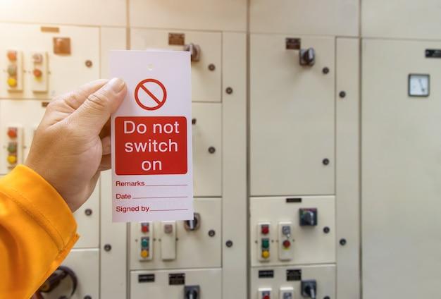 Rote tastensperre und tag in der hand für den prozess abschneiden elektrisch, die toggle-tag-nummer für die elektrische abmeldung aus