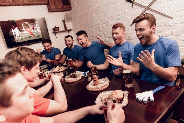 Rote teamfans sind traurig, während blaue fans in der bar sind.