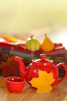 Rote teekanne mit einer tasse tee, karierten schals und gelbem herbstblatt
