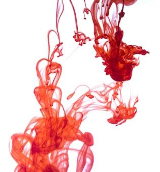 Rote tinte fiel in wasser isoliert auf weißem hintergrund.