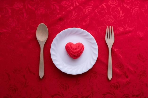 Rote tischdecke mit herzformzeichen auf platte, valentinsgrußtageshintergrund.