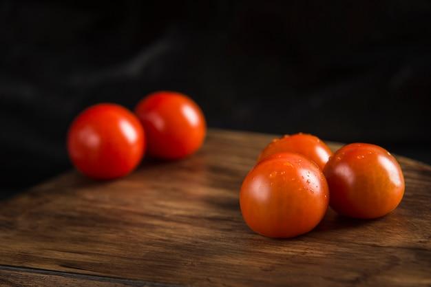 Rote tomate auf dunkler nahaufnahme des hölzernen brettes