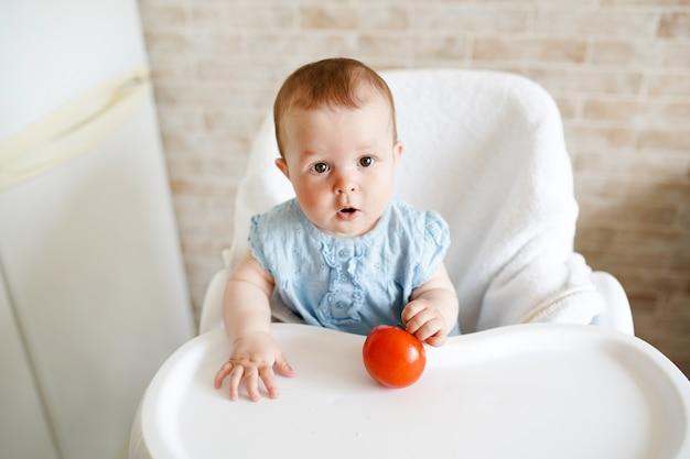 Rote tomate in der hand des kleinen mädchens in der sonnigen küche.