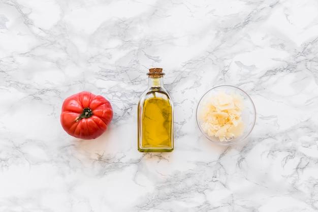Rote tomate mit olivenölflasche und geriebenem käse in der schüssel auf weißem marmorhintergrund