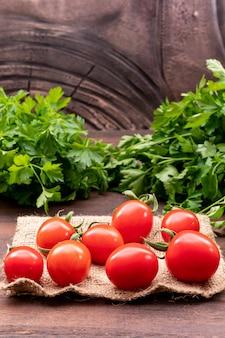Rote tomaten auf entlassung mit petersilie aus holz