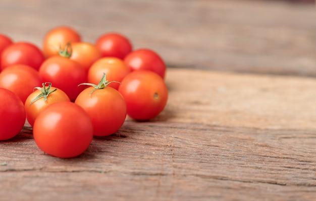 Rote tomaten der gruppe auf dem holztisch