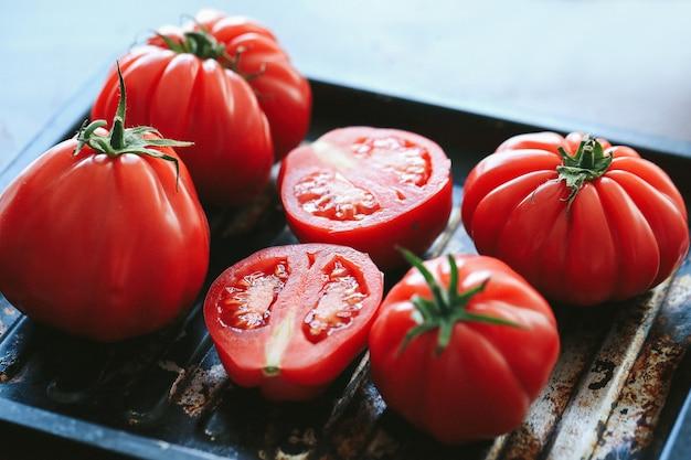 Rote tomaten, die auf der schwarzen pfanne grillen