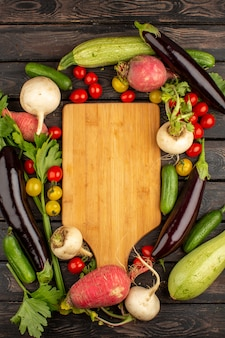 Rote tomaten frisch und reif anderes gemüse wie roter rettich und schwarze auberginen auf einem rustikalen holzboden