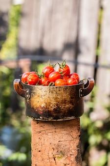 Rote tomaten in einer alten schüssel auf einem hölzernen brett draußen