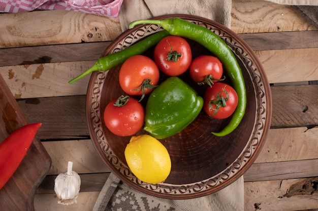 Rote tomaten in einer braunen platte mit grünem chili und zitrone