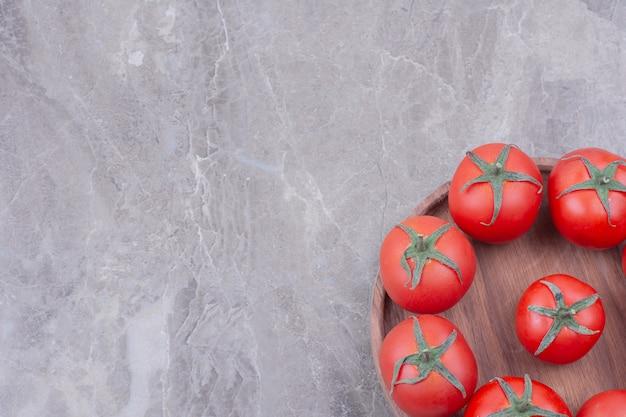Rote tomaten in einer holzplatte auf marmor.