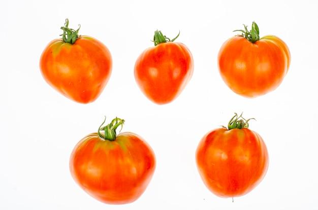 Rote tomaten in form von herzen auf weißem hintergrund. studiofoto.