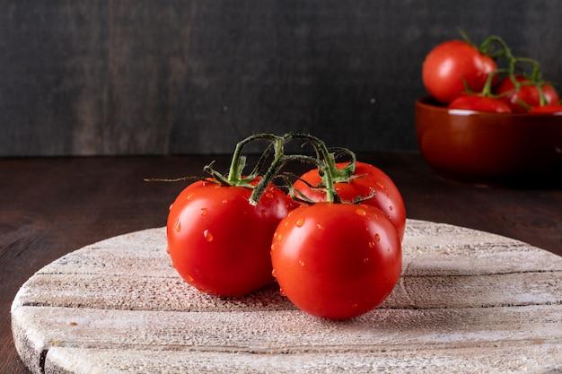 Rote tomaten mit wassertropfen und blättern des frischen basilikums auf einem organischen lebensmittel des hölzernen schneidebretts